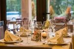 Dekoracja stołów na przyjęcia w postaci obrusu z serwetkami i świecami